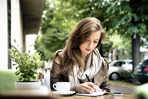 Young woman sitting in street cafe writing in her notebook - FX000021