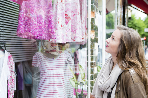 Germany, young woman looking at clothes in window display - FX000020