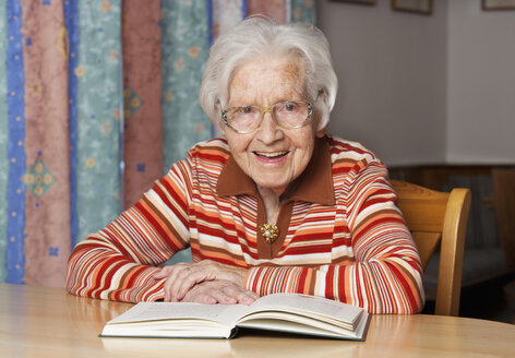 Portrait of smiling senior woman with opened book - WWF003335