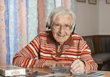 Portrait of smiling senior woman hearing CDs with headphones - WWF003340