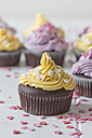 Chocolate muffins with lemon curd decorated with baking dekor on white wood - YFF000178