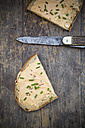 Two halves of slice of bread with obazda sprinkled with chives and knife on dark wood - LVF001435