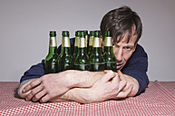 Man at table surrounded by beer bottles - MUF001495