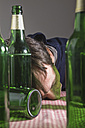 Man lying on table surrounded by beer bottles - MUF001503