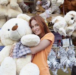 Happy young woman on a funfair hugging large teddy bear - RHF000370