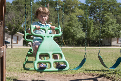 USA, Texas, Toddler on a playground swing - ABAF001392