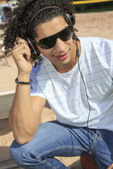 Portrait of a young man listening music on the beach - VTF000296