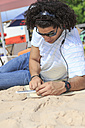 Young man with digital tablet listening music on the beach - VTF000298