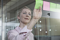 Germany, Munich, Businesswoman in office, putting sticky notes on glass pane - RBYF000517