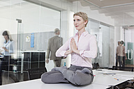 Germany, Munich, Businesswoman in office, meditating on desk - RBYF000581
