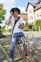 Young male student with headphones sitting on a bicycle looking at his smartphone - VTF000285