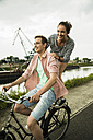 Young couple driving together on bicycle - UUF001046