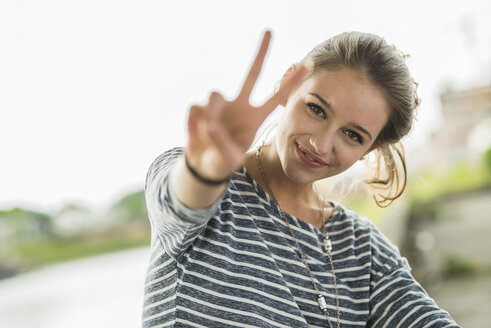 Portrait of happy teenage girl showing Victory sign - UUF001019