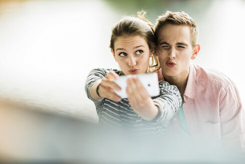 Young couple taking a selfie with smartphone - UUF001026