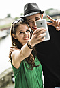 Young couple taking a selfie with smartphone - UUF001094