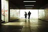 Young couple running together in a dark underpass - UUF001072