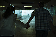 Young couple running hand in hand in a dark underpass, back view - UUF001074