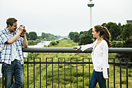 Young man photographing his girlfriend - UUF001084