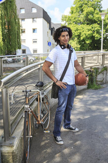 Young male student with basketball standing beside his racing cycle - VTF000291