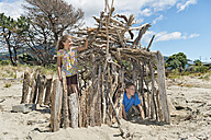 New Zealand, Golden Bay, Pakawau, girl  and boy at the beach building a house with driftwood - SHF001413