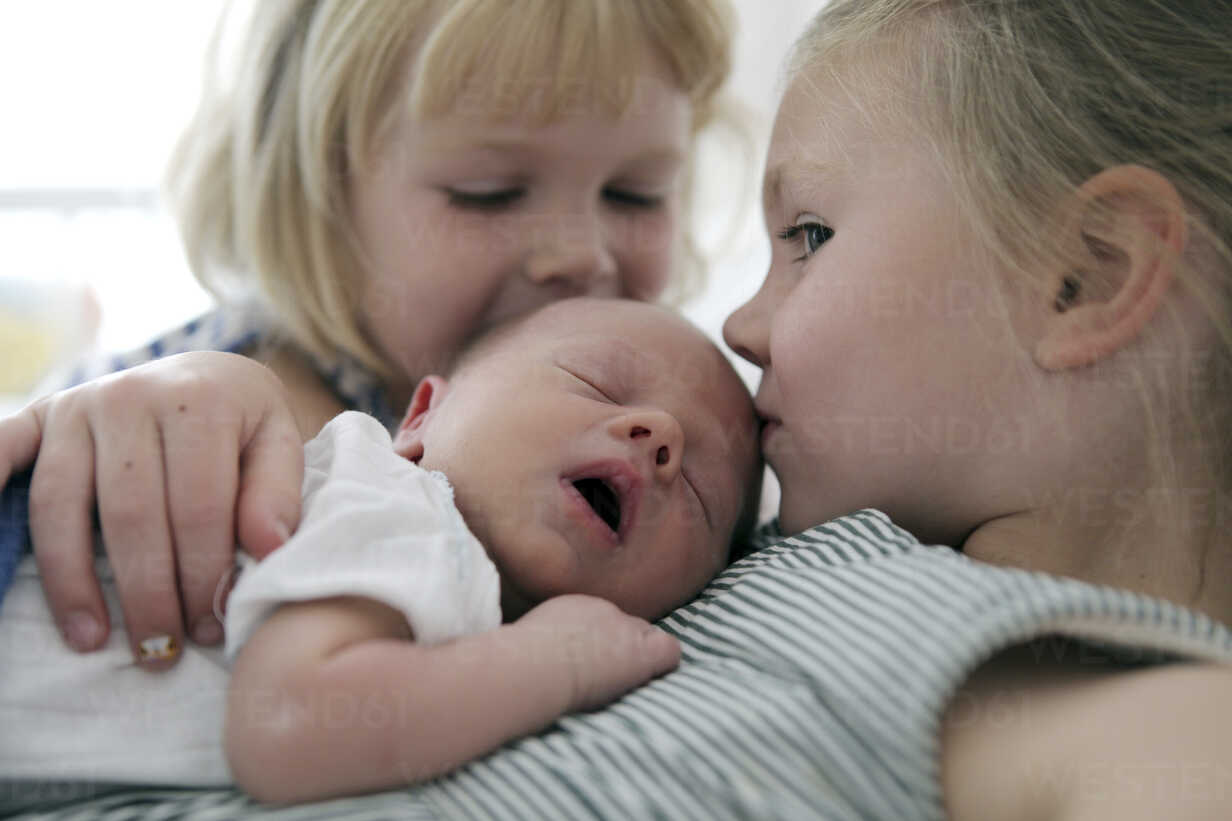 Two little girls kissing their newborn brother - SAF000015 - Anna Sauvigny/Westend61