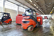 Germany, fork lift loading pallets of beer crates in a brewery - SCH000283