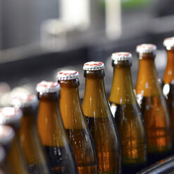 Germany, beer bottles on an assembly line of a bottling plant of a brewery, close-up - SCH000291