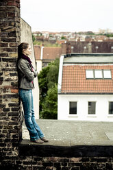 Young woman leaning against chimney on roof top - FX000025