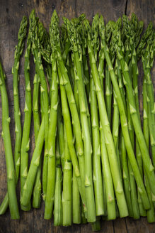 Row of green asparagus, Asparagus officinalis, lying on dark wood - LVF001447