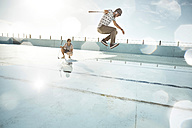 Two friends playing urban golf in empty swimming pool - VV000116