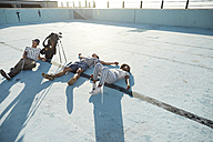 Friends lying in empty swimming pool with golf clubs - VV000120