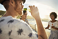 Friends drinking beer on highboard of a swimming pool - VV000126