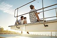Urban golfers sitting on highboard of a swimming pool - VV000128
