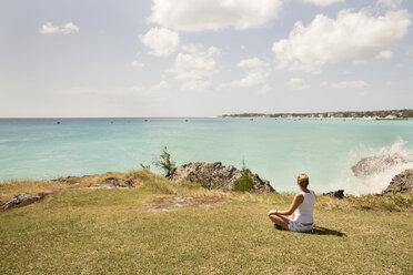 Caribbean, Barbados, woman sitting at the coast - SKF001560