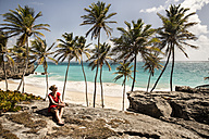 Caribbean, Barbados, Bottom Bay, woman sitting at the coast - SKF001566