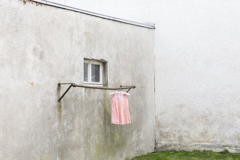 Germany, glum backyard with children's dress hanging on clothes pole - DRF000695