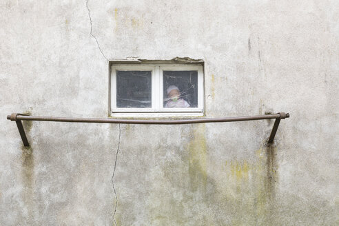 Germany, doll sitting behind window of garage - DR000697