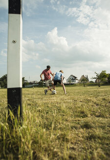 Germany, Mannheim, Father and son playing soccer - UUF001120