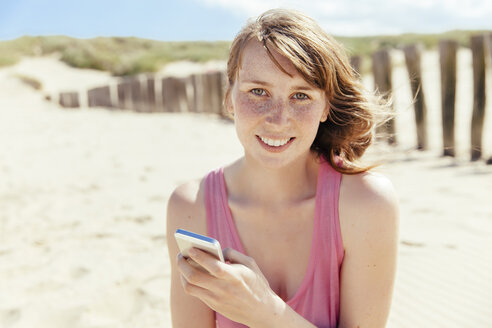 Portrait of woman with smartphone on the beach - MFF001131