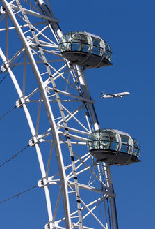 England, London, Lambeth, part of the big wheel 'London Eye' and flying airplane in front of blue sky - WE000165