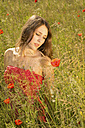 Portrait of daydreaming teenage girl on meadow with poppies - FCF000265