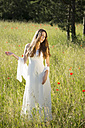 Portrait of teenage girl wearing white dress standing on meadow - FCF000268