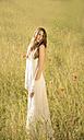 Portrait of teenage girl wearing white dress standing on meadow - FCF000270