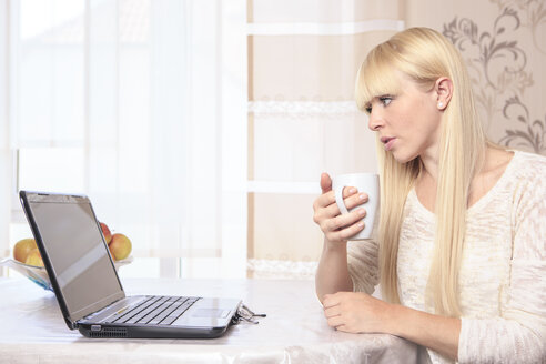 Portrait of a young woman with a cup using laptop at home - VTF000308