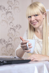 Portrait of smiling young woman with a cup and a laptop at home - VTF000305
