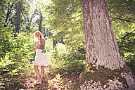 Portrait of a young woman wearing white dress standing in the forest - VTF000313