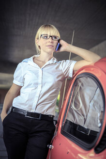 Portrait of young woman telephoning with smartphone leaning on car - VT000315