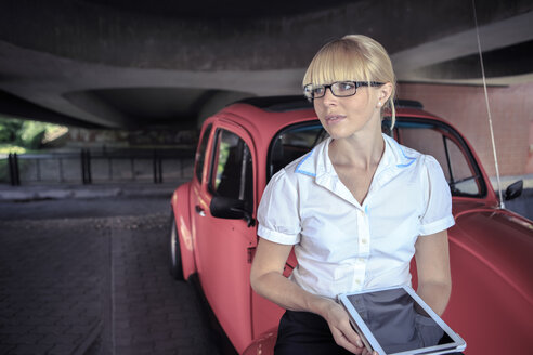 Portrait of young woman with digital tablet sittiing on bonnet of red car - VT000318