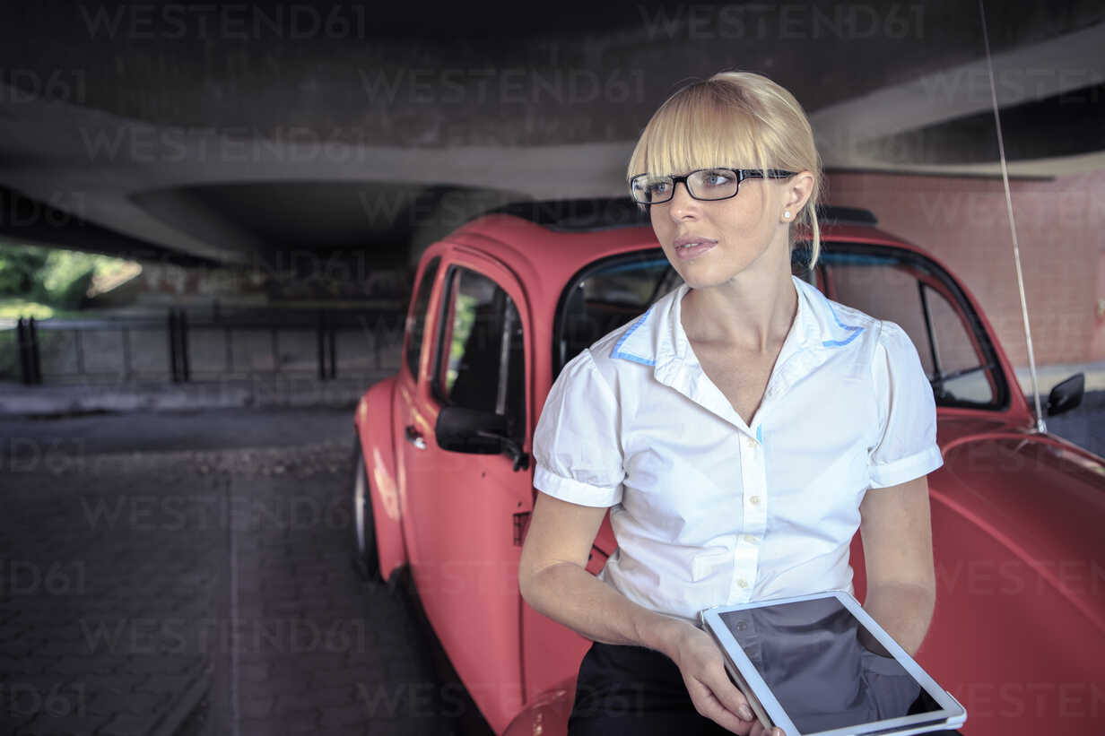 Portrait of young woman with digital tablet sittiing on bonnet of red car - VT000318 - Val Thoermer/Westend61