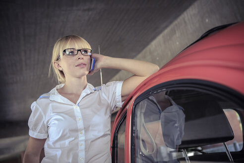 Portrait of young woman telephoning with smartphone leaning on car - VT000321